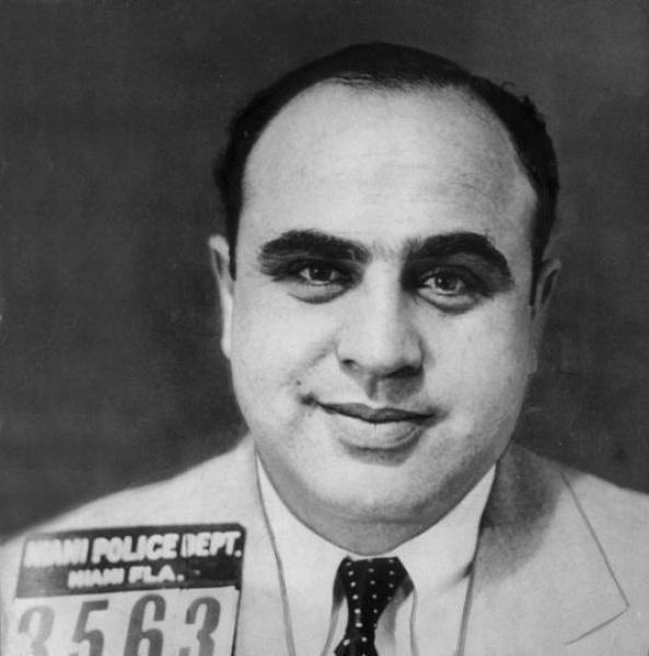 Al Capone在迈阿密被捕时的存档照片,这次逮捕当日即被释放。他所有被捕的存档照上都有他的招牌微笑。他的名言是:微笑的人办事方便,而微笑的人带把枪办事则更方便。
